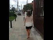 colombian puta walks barefoot in street.