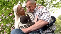 Busty blond teen gives head to a senior outdoors