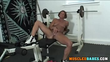 Muscled brunette masturbates in the gym