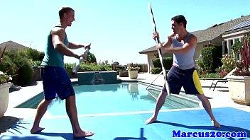 Gay muscular jocks sword fighting by the pool