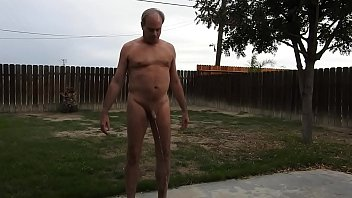 A naked daddy peeing on his back patio.