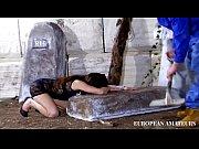 Donna vedova si consola davanti alla tomba del marito