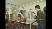 Blonde girl has her nipples bound in clamps while being tied up on a glass table Vorschaubild
