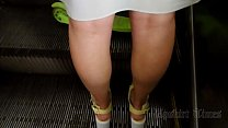 Upskirt of a slender girl on an escalator in the subway. thumbnail