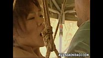 Asian slut hanging on some ropes fucked by the soldiers صورة