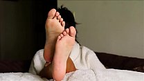 Beautiful girl takes her shoes off and shows her black feet in bed صورة