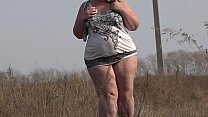 Image: A beautiful mature BBW walks outdoors and shakes a fat butt in a short dress. Fetish and exhibitionism.