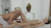 Oiled lesbians rubbing and fingering on massage table thumbnail