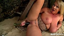 Busty seduction Laura Orsolya plays with her big round titties in the sand