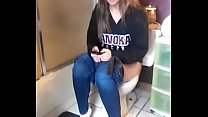 Girl on the toilet while using phone