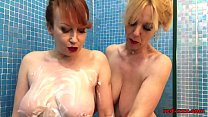 Mature redhead plays in the shower with her gir...