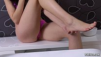 Veronika in her pink underwear slowly massages her feet and legs