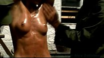 Sporty BDSM model Alex Zothberg in bondage and whipped nude by two masked men thumbnail