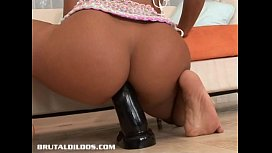 Tanned slut fills her asshole with a big black dildo