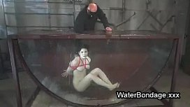 Brunette in rope bondage dive in water
