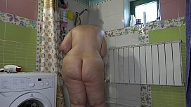 A boyfriend has set up a hidden camera in the shower room at home and is peeping at a fat girlfriend with a big ass. Amateur fetish.