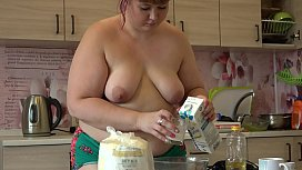Beautiful bbw with a big ass in narrow shorts bakes pancakes and gradually undresses.