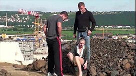 Cute petite girl is fucked in public co uction site by guys with big dicks