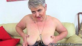 British mature Candy Cummings masturbates on sofa