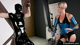 Milf domme whips male in latex suit