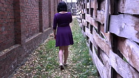Brunette with a anal plug in the ass walks on the street. Amateur fetish under a dress without panties and unusual anal pleasure.