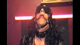 bisexual crossdresser in bondage blindfolded mouth gagged and one hand tied behind shoots a cumshot