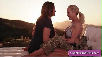 Gorgeous busty lesbian babes Kira Noir, Sinn Sage kiss tender outdoor and lick their big boobs