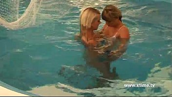 Lesbians playing with dildo in a pool