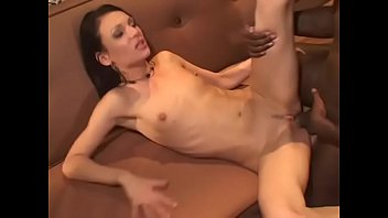 Black haired nympho rides a massive black dick on couch