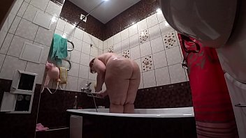 Erotic russian woman Behind the scenes, a hidden camera is spying on a fat porn model with a big ass in the bathroom.