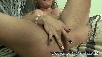 Sexy blonde tranny Tuanny spreads her legs wide and masturbates
