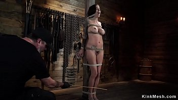 Brunette in rope bondage gets whipped