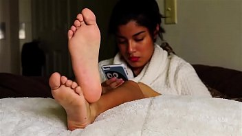 Beautiful girl takes her shoes off and shows her black feet in bed