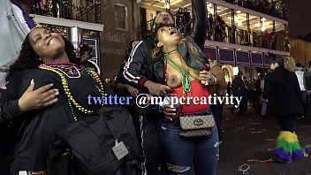Black chick flashing one tit for the crowd during mardi gras
