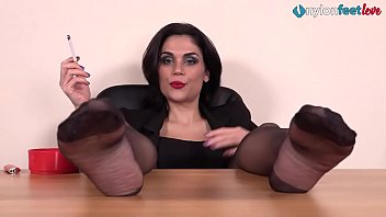 Hot brunette smokes a cig with her nylon feet up on a desk