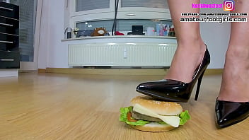 Here Kati crushes two hamburgers, she walks slowly around the hamburgers is crushing a hamburger and fruit, green apple, bananas,grapes , with high heels, ballerinas and barefoot