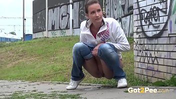 Public Peeing - Brunette babe relieves herself in front of a packed train