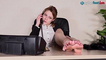Redhead secretary in stockings under the desk shoeplay