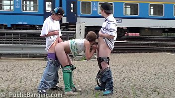 Cute young pretty teen girl public sex threesome orgy with 2 young guys fucking at a railway station with blowjob sucking dicks and vaginal pussy intercourse in front of the train passengers and strangers