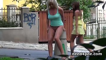 Tanned blonde pisses standing on the side walk