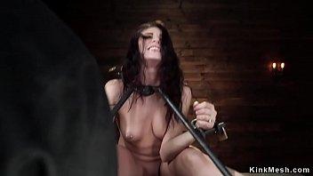 Brunette locked in metal device sitting