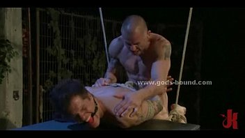 Gay master in leather costume punishing his sex slave in rough extreme bdsm