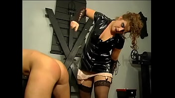 Two horny chicks in latex suits punish a muscular prisoner with a whip