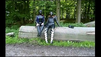 Two girls in latex touch each other