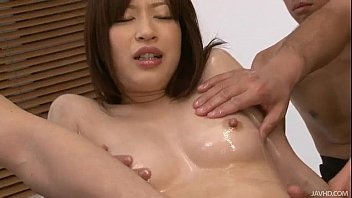 Image: Horny guys oil up Riko's shaved pussy and finger it
