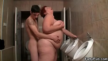 Slim guy fucks busty fatty in the restroom
