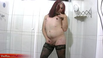 Redhead t-girl in stockings reveals plump ass and shecock
