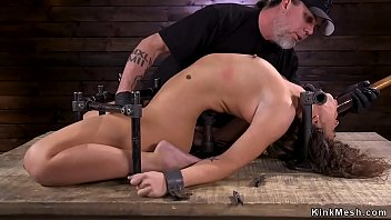 Brunette in arc bondage device