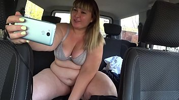 A beautiful BBW in a car near public garages shows up and masturbates in sex chat.