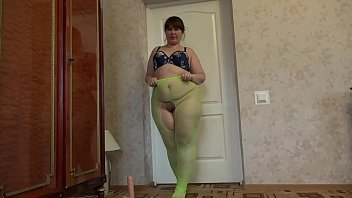 A fat girl with a big ass and a hairy pussy in green pantyhose masturbates her p